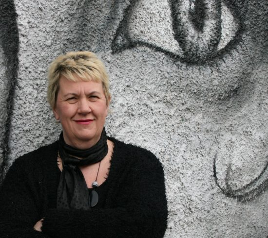 Woman standing against a mural