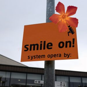 a new, less intimidating instruction to remind people they are being watched by cctv, reads 'smile on, system opera by'