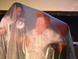 Photo of Katherine Araniello obscured by a large plastic sheet, carrying a megaphone