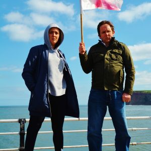Flyer image shows a male and female actress holding a St George's flag in front of a seaside railing