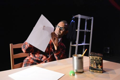 Performer Ramesh Meyyappan sits at a table holding a large piece of paper and wearing a quizzical expression