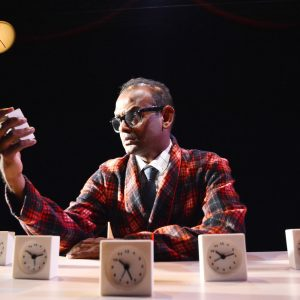 Performer Ramesh Meyyappan sits at a desk with five alarm clocks