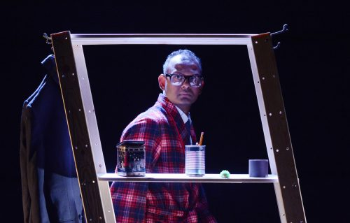Performer Ramesh Meyyappan pictured looking through an askew set of shelves