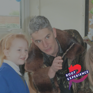 Simon Magnus, Artistic Director of Root Experience dressed as a wizard performing The Book Project with a young audience member
