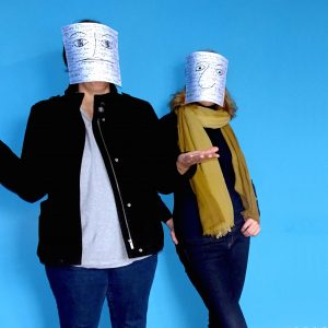 Photo of two individuals standing against a blue wall with silver buckets on their heads