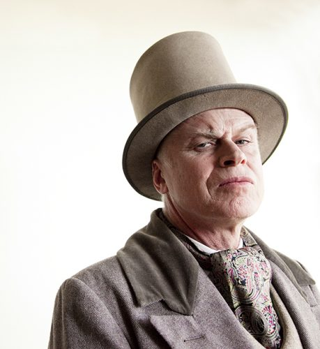 Photo of actor Graeme Rhodes dressed in Victorian hat and suit, wearing a stern expression