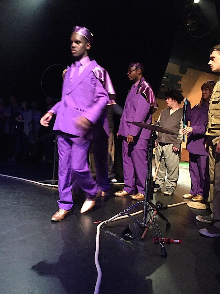 Photo of an actor dressed ina purple suit walking on to the stage