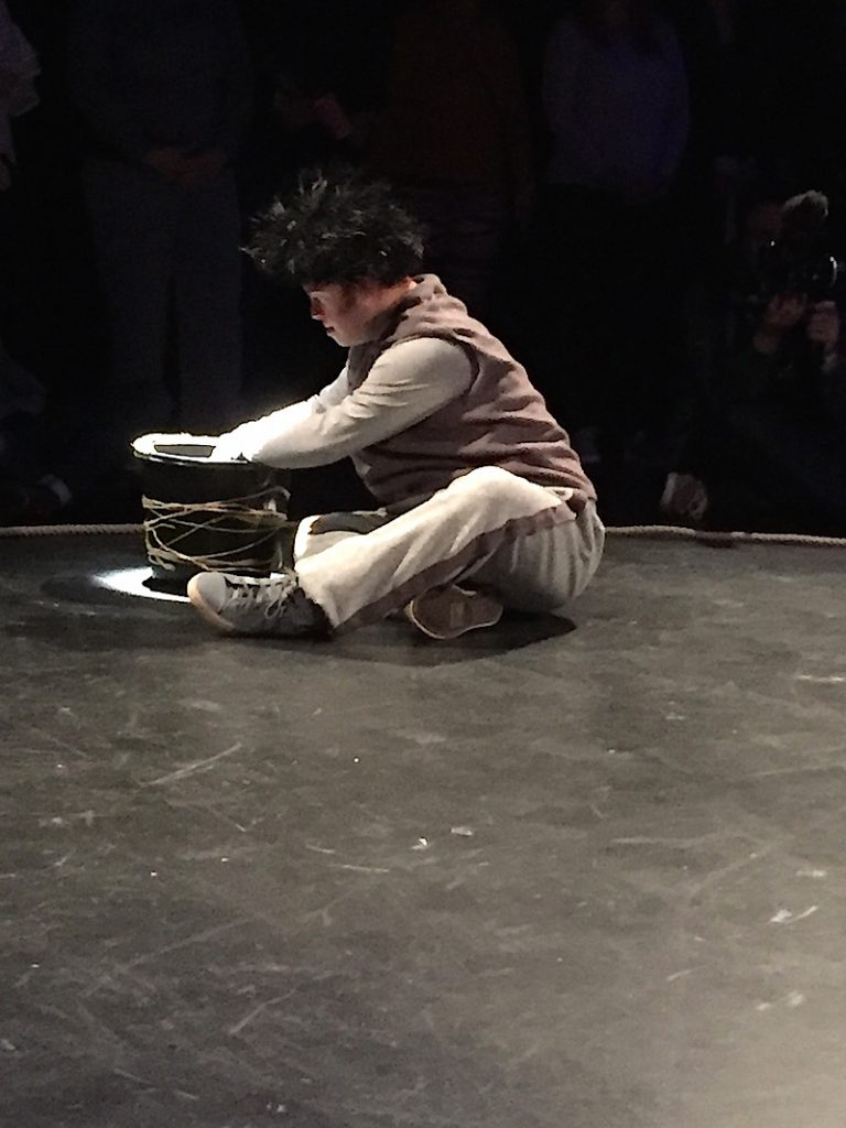 Photo of an actor sitting with a cauldron on stage at the mac