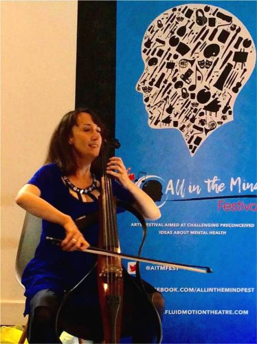 Artist Jo-anne Cox plays the cello against a backdrop of a blue All In The Mind poster