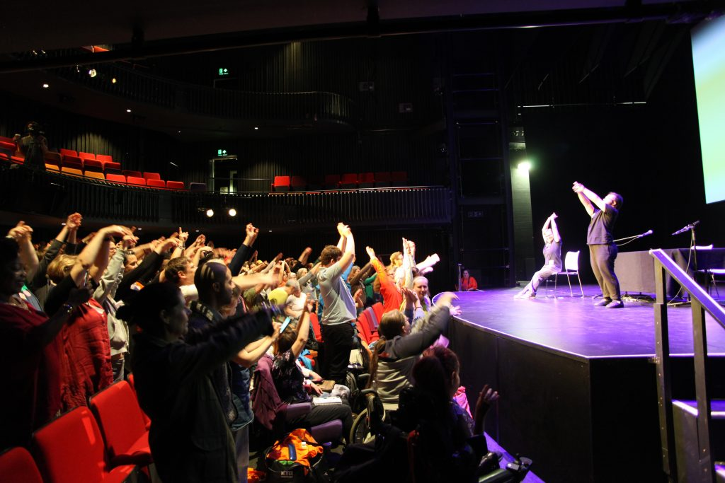 Photograph of a crowd throwing their hands in the air as they are directed to by a performer on stage