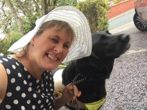 A picture of a woman in a white broad brimmed hat, black dress with white polka dots, holding her camera up in front of her. She's smiling just a little too much. On her right is a black guide dog in a white harness.