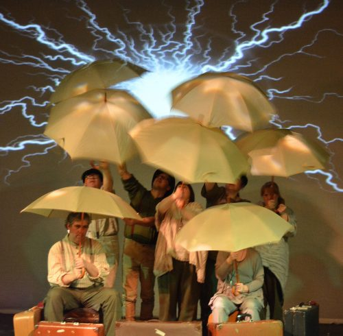Photo of an ensemble carrying large beige umbrellas, pictured with a bolt of lightning behind them