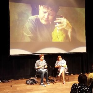 Photo of Brian Lobel & Ruth Gould on stage in front of a screening of Julie McNamara