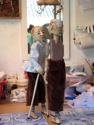 two puppets facing each other, not fully dressed yet.
