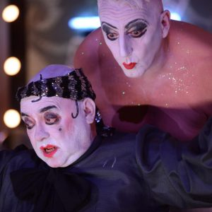 Photo of two actors dressed in white face paint, staged in a theatre dressing-room