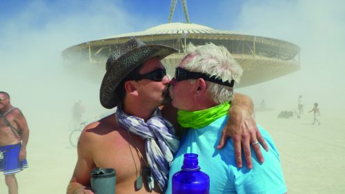 Photo of two men kissing in front of a ferris wheel