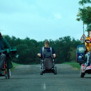 Photo of three male wheelchair-users on a road