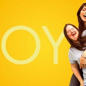 Photo of actress Imogen Roberts, pictured smiling against a yellow backdrop with the word JOY, written on it
