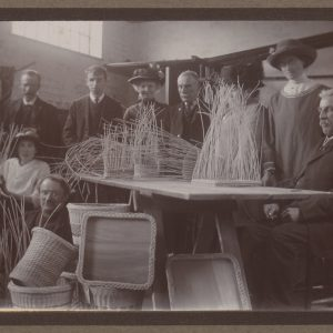 Archive black and white photo of a group of people standing behind a bench for basket weaving