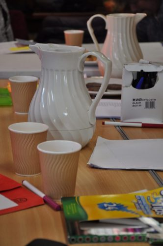 Photo of jugs and cups on a table with writing implements