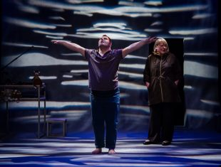 Photograph of Nathan Bessell as Matty in Up Down Man, he has his arms outstretched and the set is lit in black and white