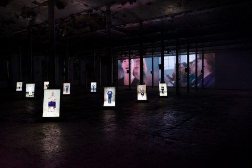 photo of a film installation showing a series of photoportraits in a dark background. A film shows on the wall in the background