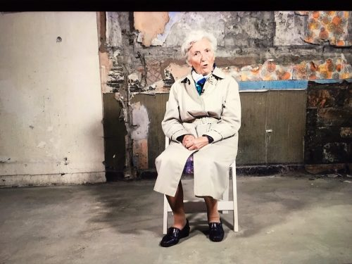 Photo of an elderly woman sat on a chair whilst talking to the camera