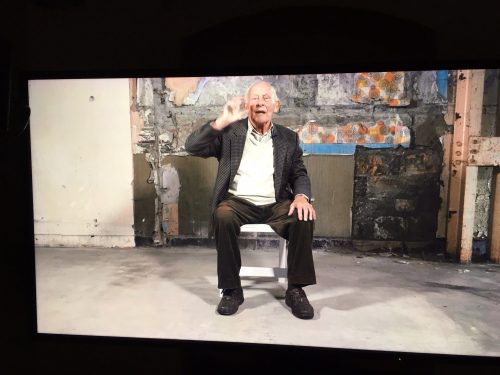 Photo of an elderly man sat on a chair whilst talking to the camera