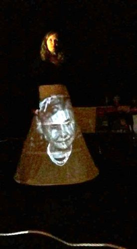 A black and white image of Helen Keller projected onto actor, Tam Gilbert's skirt, as part of 'Practice' at Salisbury Arts Centre. Tam is standing with her face dimly lit, half is in shadow.