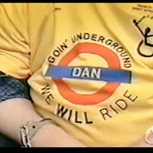 "Photo of the front of a yellow DAN t-shirt with the London underground logo and the words ""we will ride""."