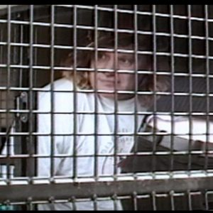 Photo of activist behind bars during a disability protest