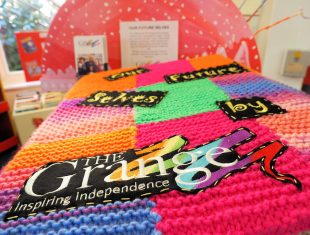 Photo of a brightly coloured knitted patchwork book with the title Our Future Selves by The Grange embroidered onto it.