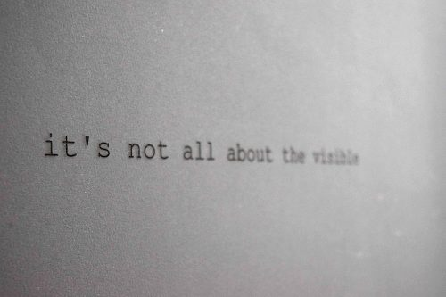 Subtle black text on a sheet of paper, reads: 'It's not all about the visible'
