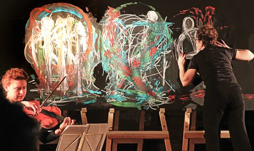 Photo of visual artist Rachel Gadsden creating live painting on a series of black canvases