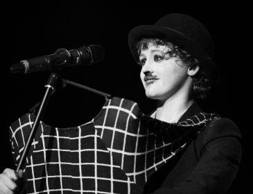 Blacka nd white photograph of a woman who looks like she is dressed as Charlie Chaplin