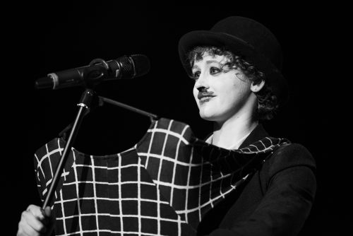Blacka nd white photograph of a woman who looks like she is dressed as Charlie Chaplin