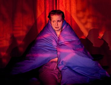 Promotional image from You've Got Dragons showing a young woman with a purple duvet wrapped around her shoulders, in the background a red backdrop has images projected onto it
