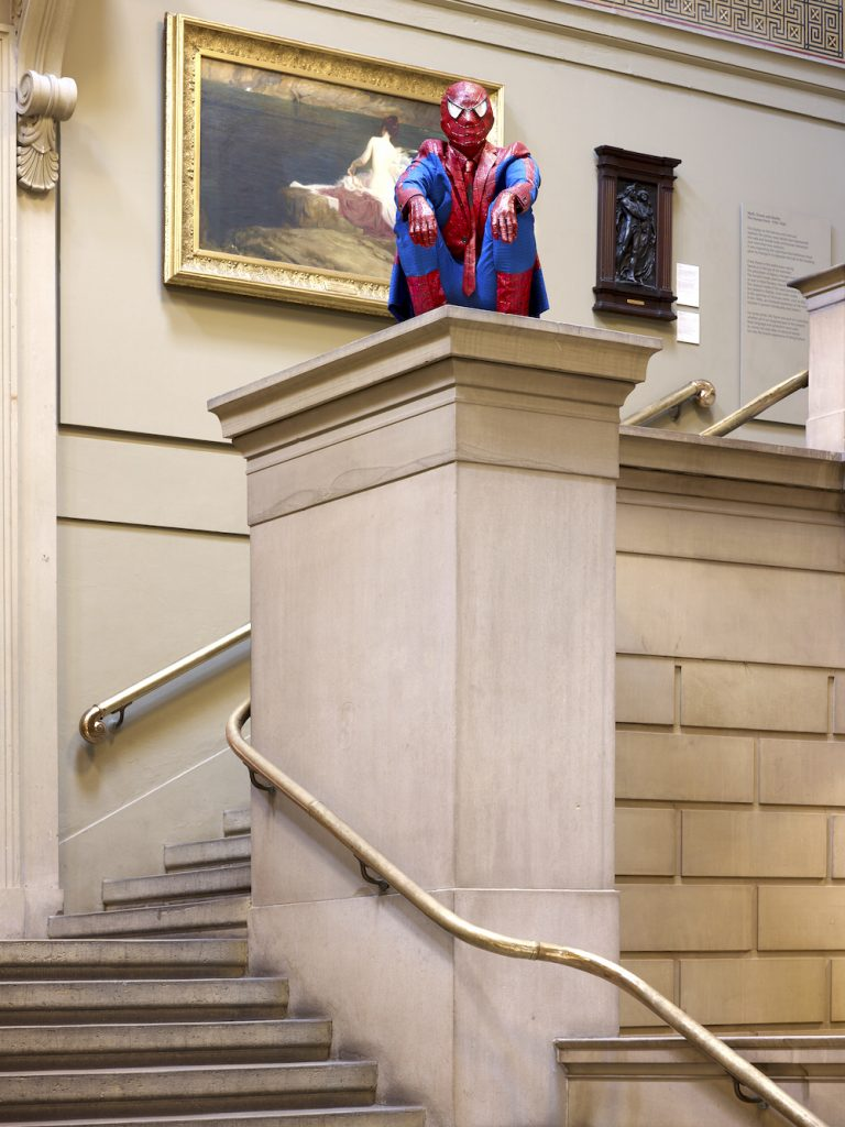 Photo of a figure dressed as Spider Man, seated on a podium overlooking a stairwell within the gallery