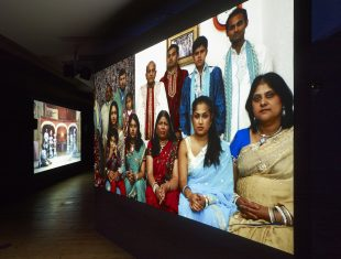 Photo of a film installation in a darkened gallery space showing a still of a group of Indian people