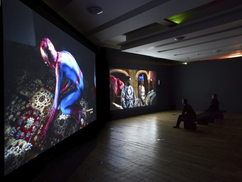 Photo of a film installation in a darkened gallery space showing an image of Spider Man