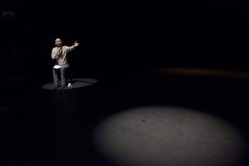 Man sitting under a spotlight