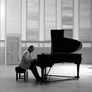 Black and white photo of composer Waseem Kotoub , sitting at a grand piano