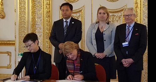 A group of dignitaries sign an agreement in a palatial setting