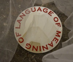 A circular artwork with the words: 'Language of meaning of language' in red on a white background