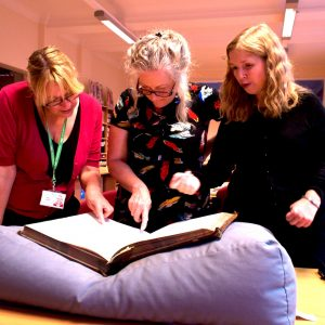 Group of women looking at a large book of records