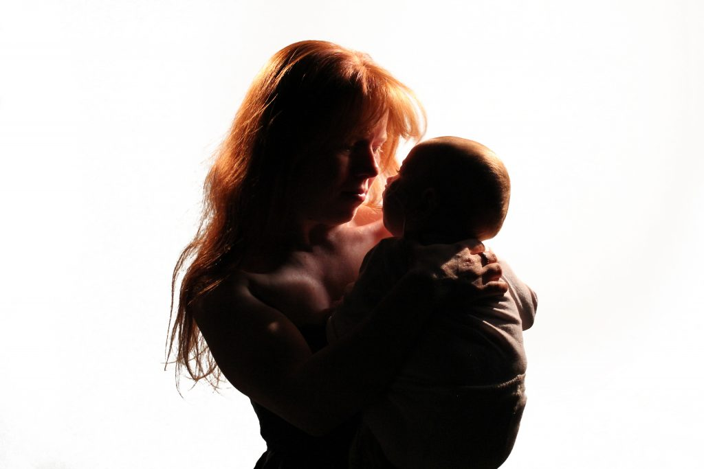 A partially silhouetted image of a young woman holding a baby