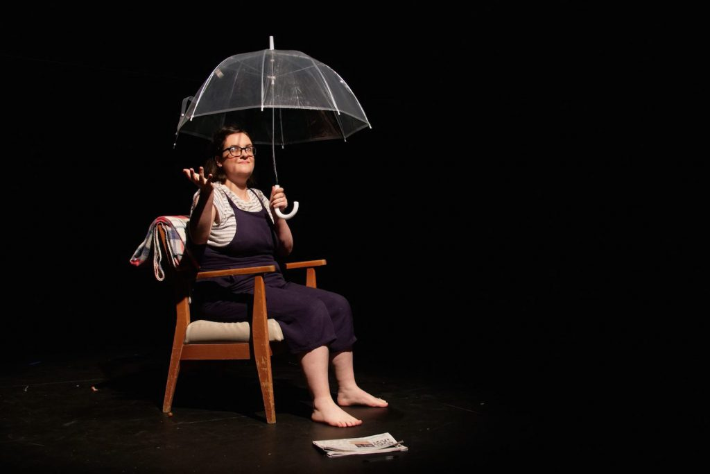 Photo of a young woman sitting in a chair holding an umbrella