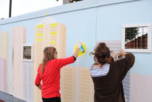 Photo of two women spray-painting a mural on a wall