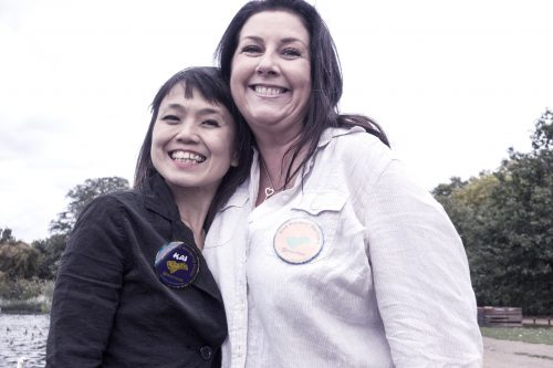Two women wearing abdges smile at the camera