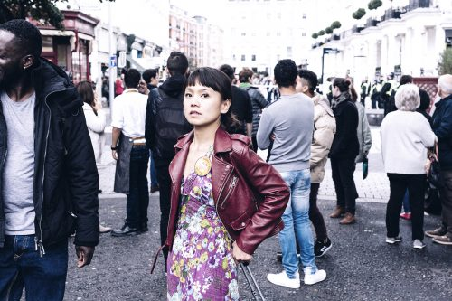 Woman looking at camera in front of a gathered crowd